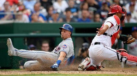 Mets' Jeff McNeil, left, slides home to score