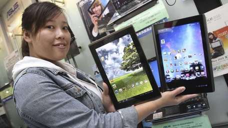 A showroom employee displays tablet computers from Taiwan's