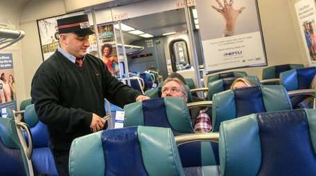 LIRR conductor Anthony Massa collects tickets on an