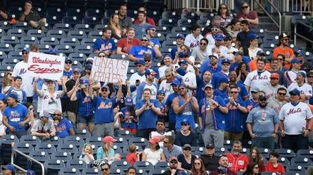 Mets fans hold up signs during a game