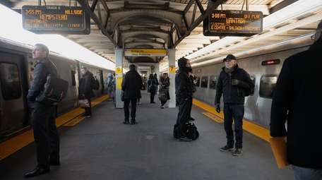 Passengers wait at the Jamaica station platform on