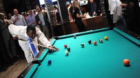 New York Giants player Justin Tuck plays pool