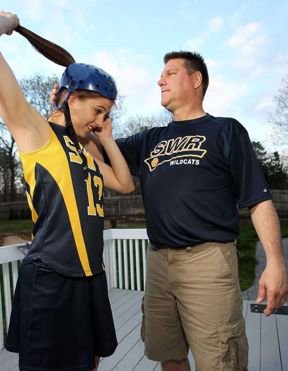 Chris Fehmel helps his daughter, Alexandra, put on