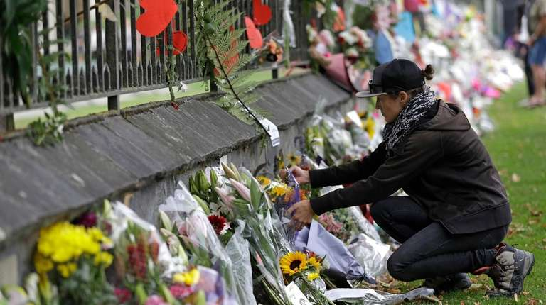 A woman pauses as she lays flowers on