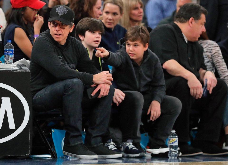 Actor Ben Stiller, left, watches an NBA basketball
