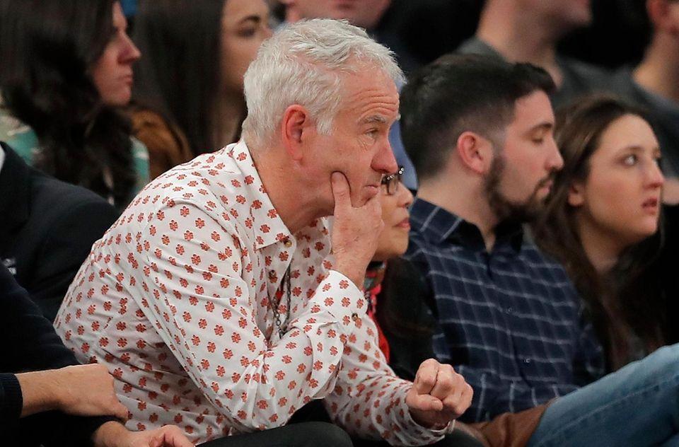 John McEnroe watches an NBA basketball game between