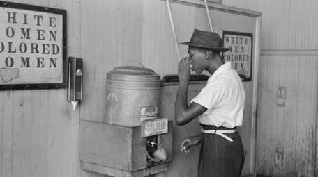 "A man drinks at a ""Colored"" water cooler"