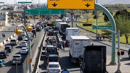 Cars and trucks line up to enter Mexico