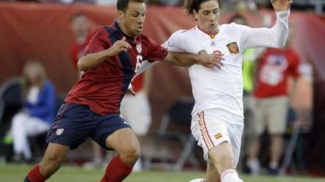 Spain's Fernando Torres, right, shoots and scores despite