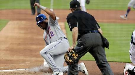 The Mets' Dominic Smith scores on a ground
