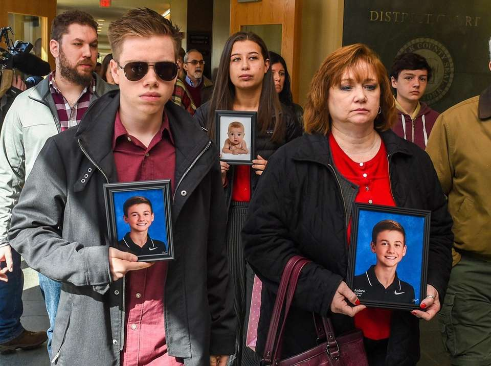 Family and friends of Andrew McMorris, hold pictures