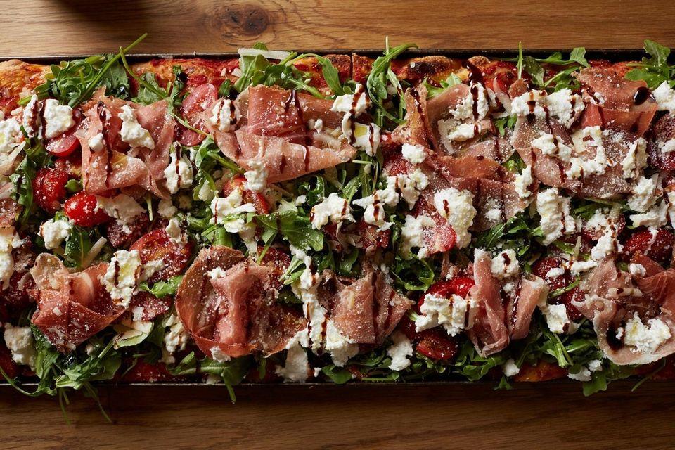 Prosciutto and arugula top a Roman-style pizza at