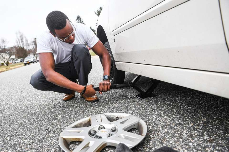 Orlando Ramos, of Northport, changes his vehicles tire