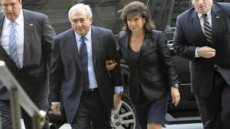 Dominique Strauss Kahn, second left, enters Manhattan criminal