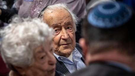 Jack Baumfeld, center, a Holocaust survivor, and his