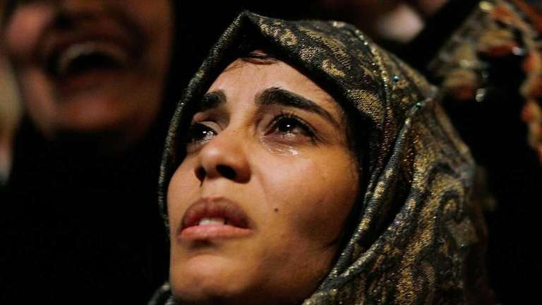 A woman cries in Tahrir Square after it