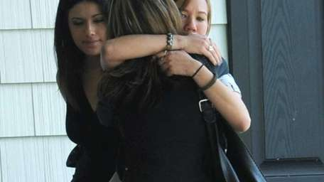 Mourners console one another outside the Robertaccio Funeral