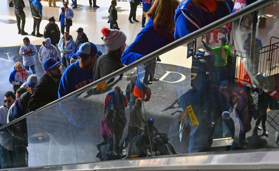 Mets fans arrive on the escalators at the