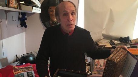 Pro wrestling journalist Bill Apter holds cassettes of