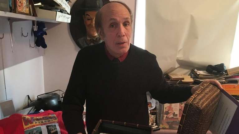Pro wrestling journalist Bill Apter holds cassettes of