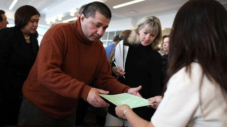 A job seeker collects employment pamphlets during the