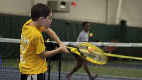 8-year-old Gregory Weinstein takes a swing after spending