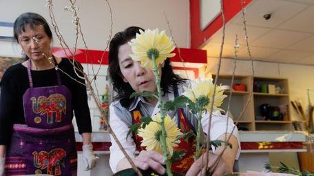 Ikebana instructor Toyomi Sobue, right, helps Alma Davis-Carlin