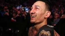 Champion Max Holloway leaves the octagon after defeating
