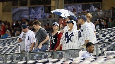 Fans wait out a rain delay of the