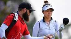 Annie Park selects a golf club during the