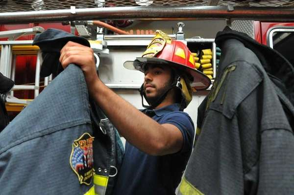 Firefighter Joshua Banilivy, 18, hangs up his uniform