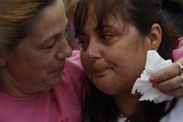 Lorraine Ela holds Lynn Barthelemy. The bodies of