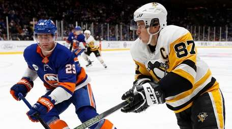 The Penguins' Sidney Crosby skates against the Islanders'