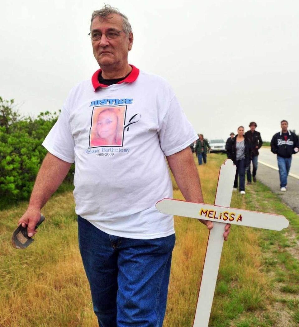 Elmer Barthelemy carries a cross as he approaches