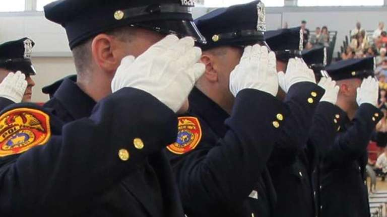 Suffolk County Police Officers salute during their graduation