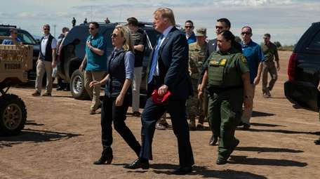 Homeland Security Secretary Kirstjen Nielsen walks with President