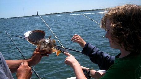 Showing off a fish caught at Cedar Beach