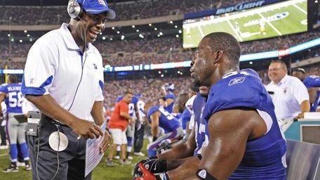 Giants defensive coordinator Perry Fewell, left, talks to
