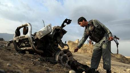Afghan security forces check the bomb site Tuesday,
