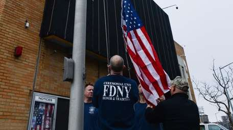 Firefighters set the flag to half-staff in front