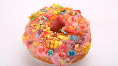 A doughnut topped with colorful cereal pieces from
