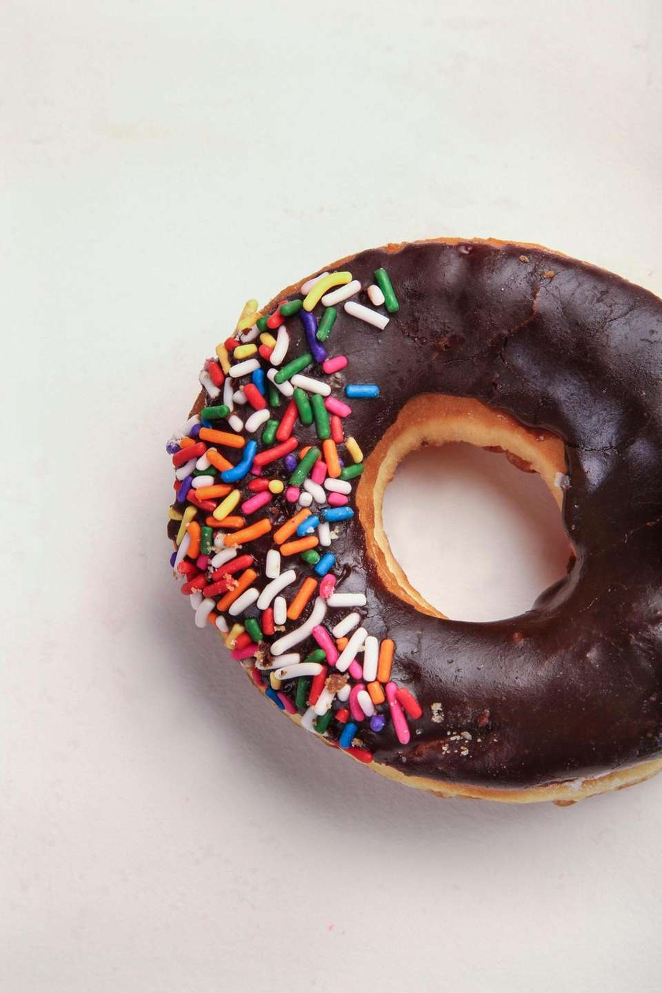 A chocolate covered doughnut with sprinkles from House