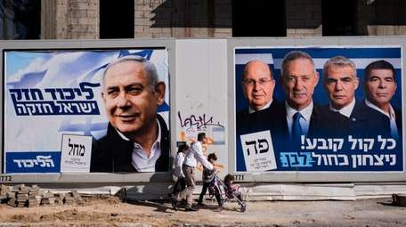 People walk by election campaign billboards showing Israeli