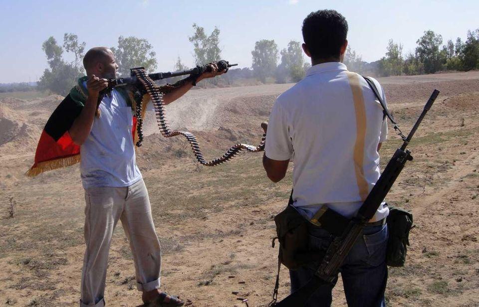 Rebel fighters fire their machine guns towards pro-Moammar