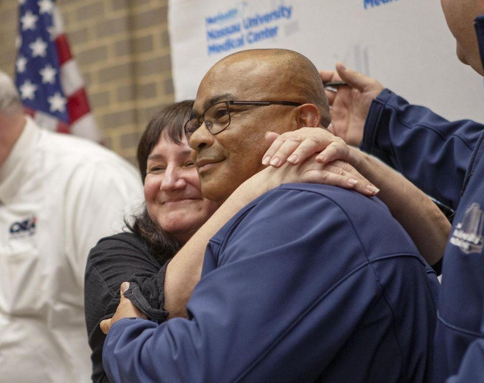 Tracy DeLuca hugs Michael Rayson as Nassau University