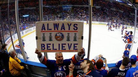 Islanders fans cheer their team as they warm
