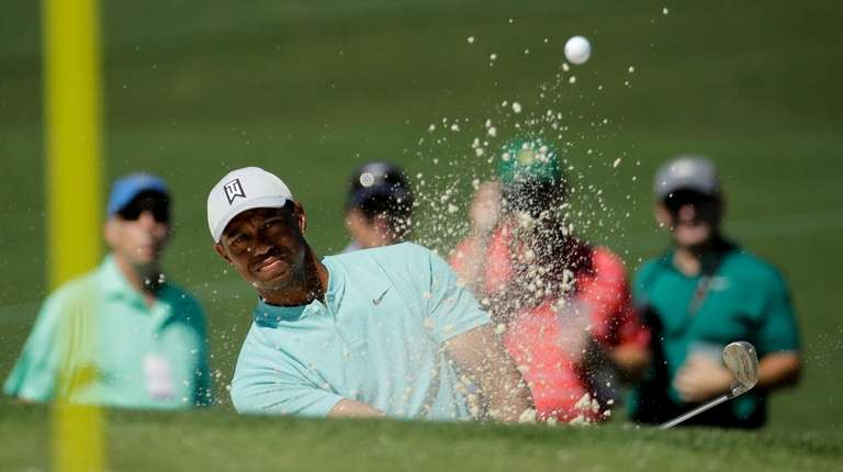 Tiger Woods hits out of the bunker on