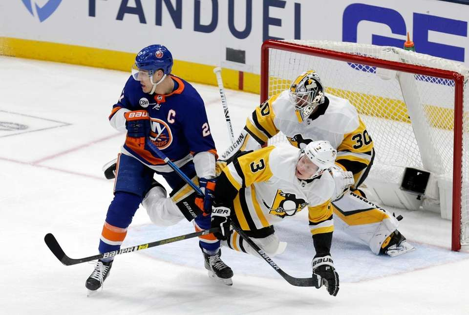 Islanders left wing Anders Lee (27) battles in
