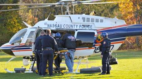 A Nassau police aviation unit helicopter transports an