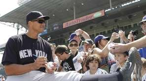Yankees third baseman Alex Rodriguez signs autographs for